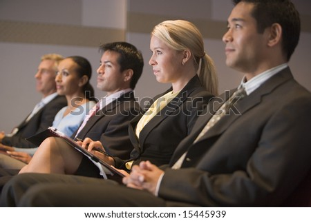 Five businesspeople sitting in presentation room with clipboards - stock photo