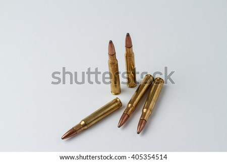 Five .30-06 caliber hunting rifle ammunition cartridges in a random arrangement - stock photo