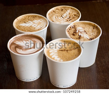 five cappuccino cups over wooden table - stock photo
