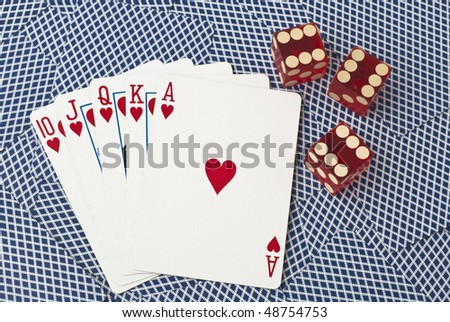 Five cards and three dice, showing a royal flush with hearts from ten to ace, on a background of backsides of blue playing cards. The dice all show number six