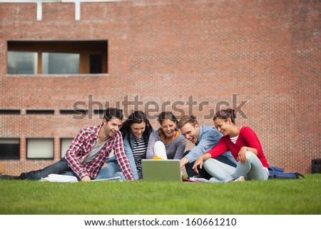 Five casual students sitting on the grass pointing at laptop on campus at college - stock photo