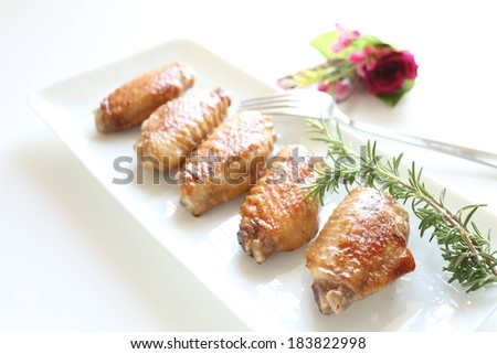 Five chicken wings sitting on a long white dish. - stock photo