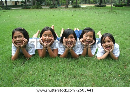 Five children playing in the park. - stock photo