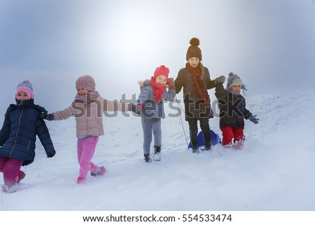 Five children run and play in a snow. Pulling sleds. Space for copy.