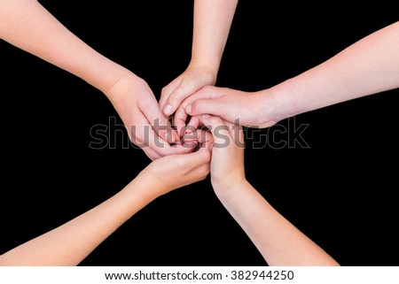Five children's arms with hands entwined isolated on black background - stock photo