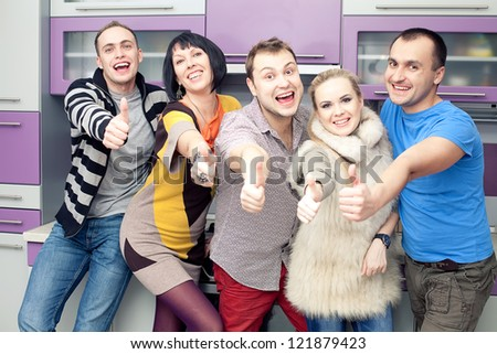 Five close friends enjoying a social gathering together and showing thumbs up happily at home (kitchen room). Indoor shot.