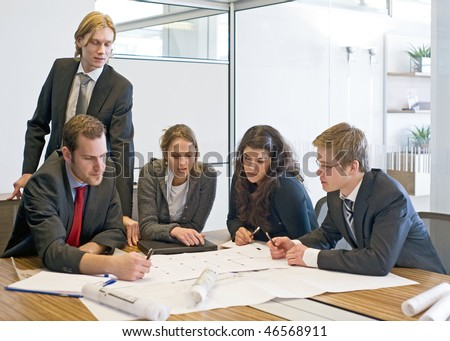 Five colleagues going over blue prints - stock photo