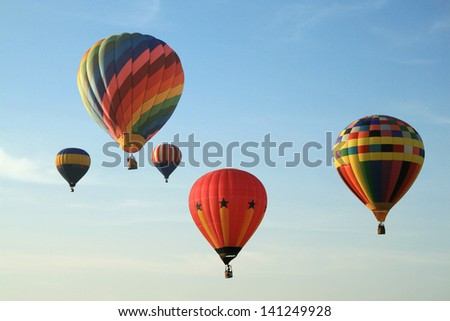 Five colorful balloons floating in blue sky.
