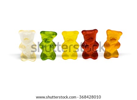 Five colorful gummy bears or jelly bears in a row in funny poses with shadows on white background - stock photo