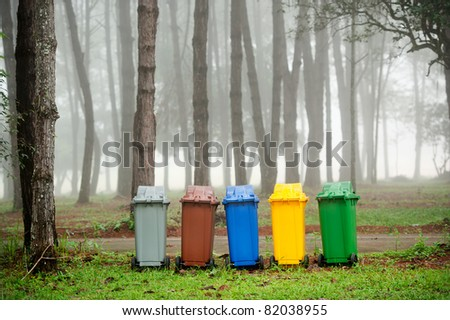 five colors recycle bins in pine forest - stock photo