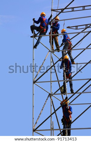 Five construction workers building a metallic scaffold - stock photo
