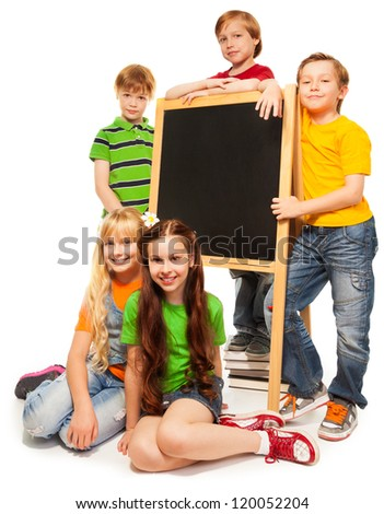 Five cute school kids with blackboard isolated on white - stock photo