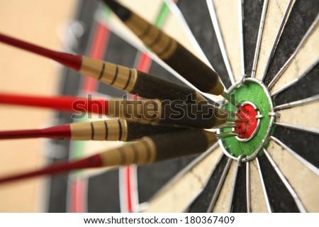 five darts hitting bullseye on dartboard stock photo edit now