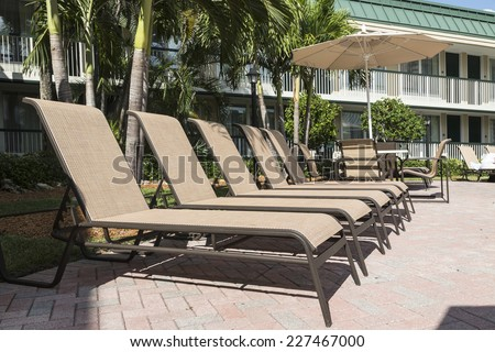 Five deck chairs with a parasol for sunbathing by the pool. - stock photo