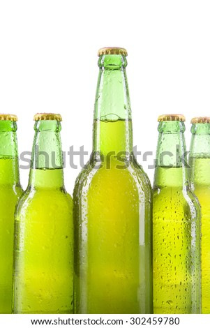 Five dewy bottles with cold and fresh lager, isolated over white background