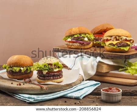 Five different gourmet burgers on wooden background - stock photo