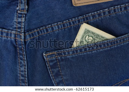 five dollars in blue jeans pocket - stock photo