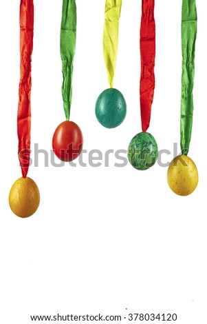 Five Easter eggs hanging on ribbons of color with a white background