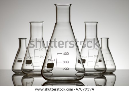 five empty flasks on a white backlight