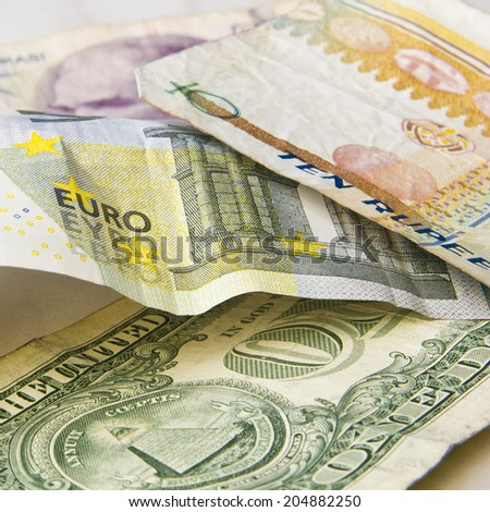 Five euro and one dollar used blended paper money banknotes on a bright background with some other world banknotes. - stock photo