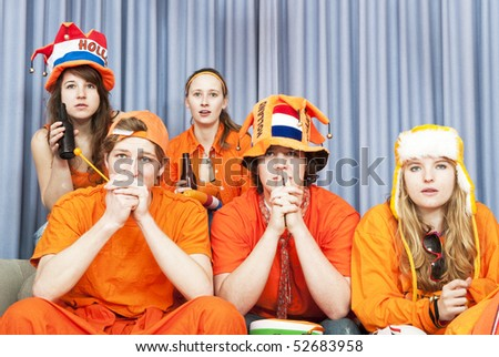 Five fans watching a game at home looking tense and nervous - stock photo