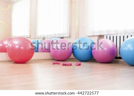 Five Fitballs and Barbells On Floor in Sport Fitness Center Indoors. Horizontal Image Orientation