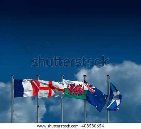 Five flags flying against a summer sky; flags or France, England, Wales, Australia and Scotland