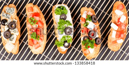 Five fresh bruchettas from above - stock photo