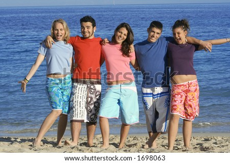 Five friends in different coloured t-shirts,goofing about at beach - stock photo