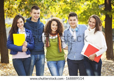 Five friends standing in front of school and smile - stock photo