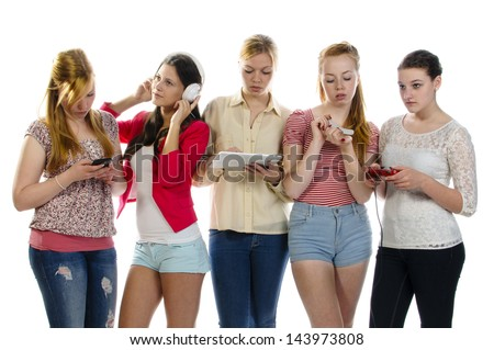 Five girls standing together, each is busy with another activity: use your cell phone, listen to music with headphones, tablet pc, filing nails with a nail file and plays video games. Isolated - stock photo