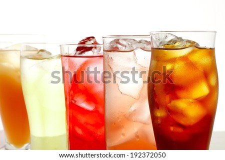 Five glasses containing different colored liquids lined up in a row. - stock photo