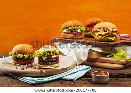 Five gourmet burgers on bright orange background - stock photo
