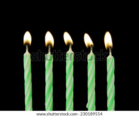 Five green burning candles on black background