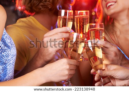 Five hands raising champagne flutes in a toast   - stock photo