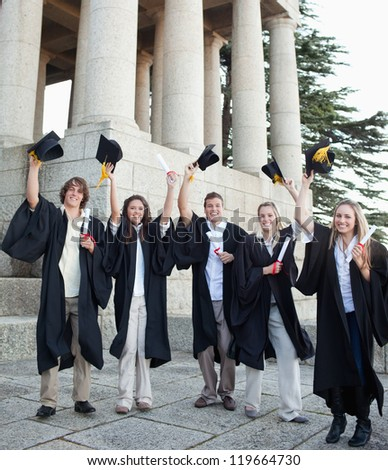 Five happy grad students raising their hats in front of the university