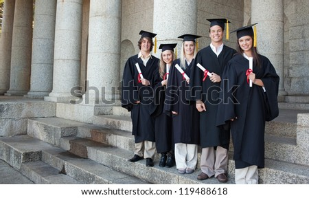 Five happy graduates posing in front of the university