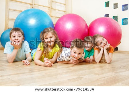 Five happy kids lie in gym with large balls - stock photo