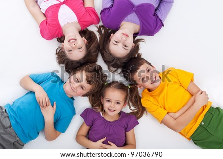 Five happy kids on the floor laying in circle - stock photo