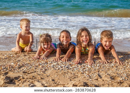Five happy kids stretched out his arms on the beach - stock photo