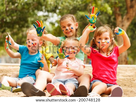 Five happy kids with hands covered in paint - stock photo