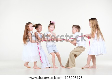 Five happy little children in white clothes draw over pink rope. - stock photo