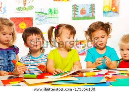 Five happy little 3-4 years old kids sitting by the table on creative paint an glue lesson - stock photo