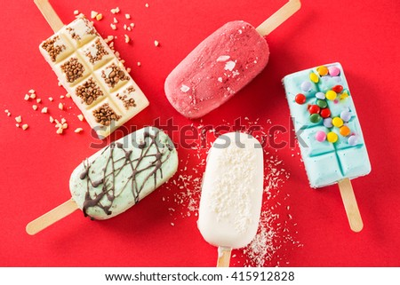 Five ice creams with different tastes on red background.From above - stock photo