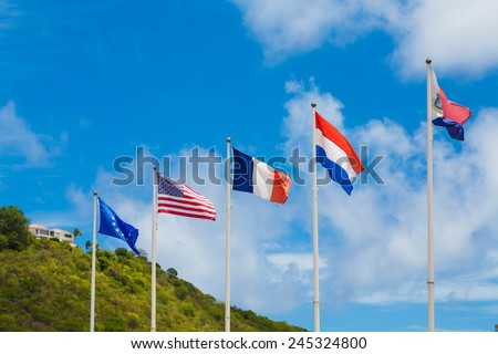 Five international flags flying under blue sky in the Caribbean - stock photo
