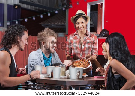 Five laughing friends sharing plate of pizza
