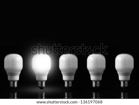 Five light bulbs in line against black background - stock photo