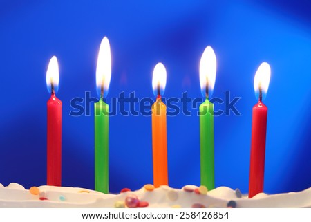 Five lit birthday candles close up, shallow dof - stock photo