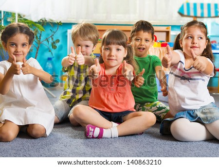 Five little children sitting on floor with thumbs up sign - stock photo