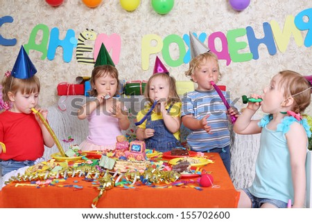 Five little kids sit at red table with cake and blow in multicolor party blowers at birthday party. Inscription Happy Birthday on wall. - stock photo
